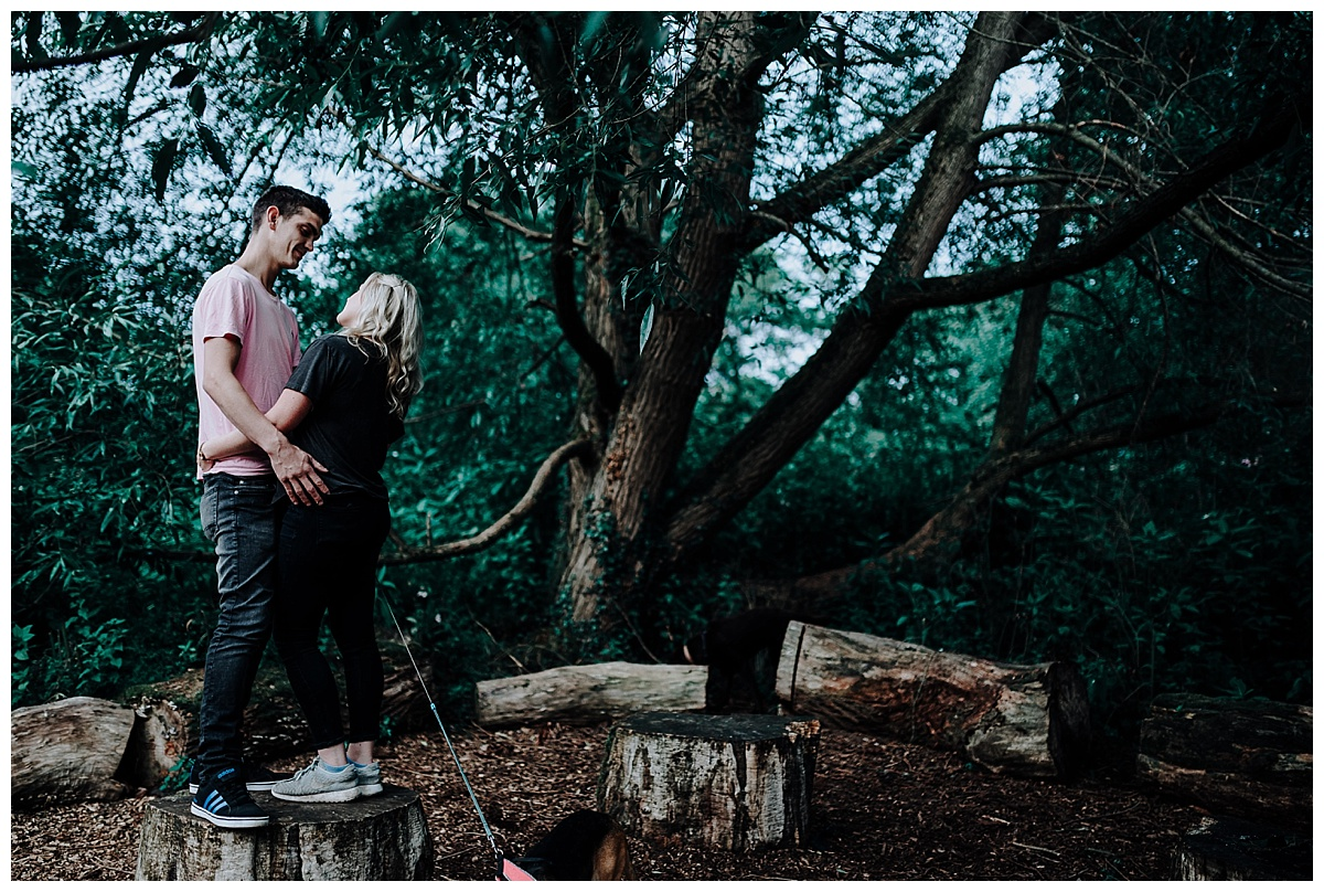 Vicky & Mathew standing on a log smiling on their pre-wedding session