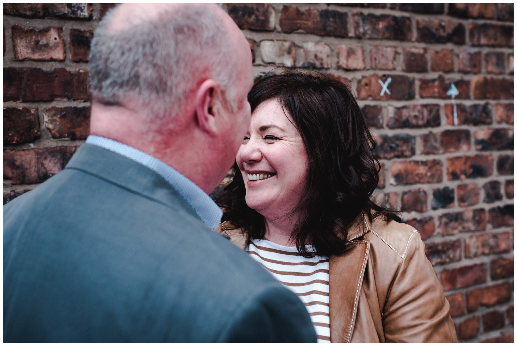 Allison laughing in front of brick wall in Manchester on pre-wedding session