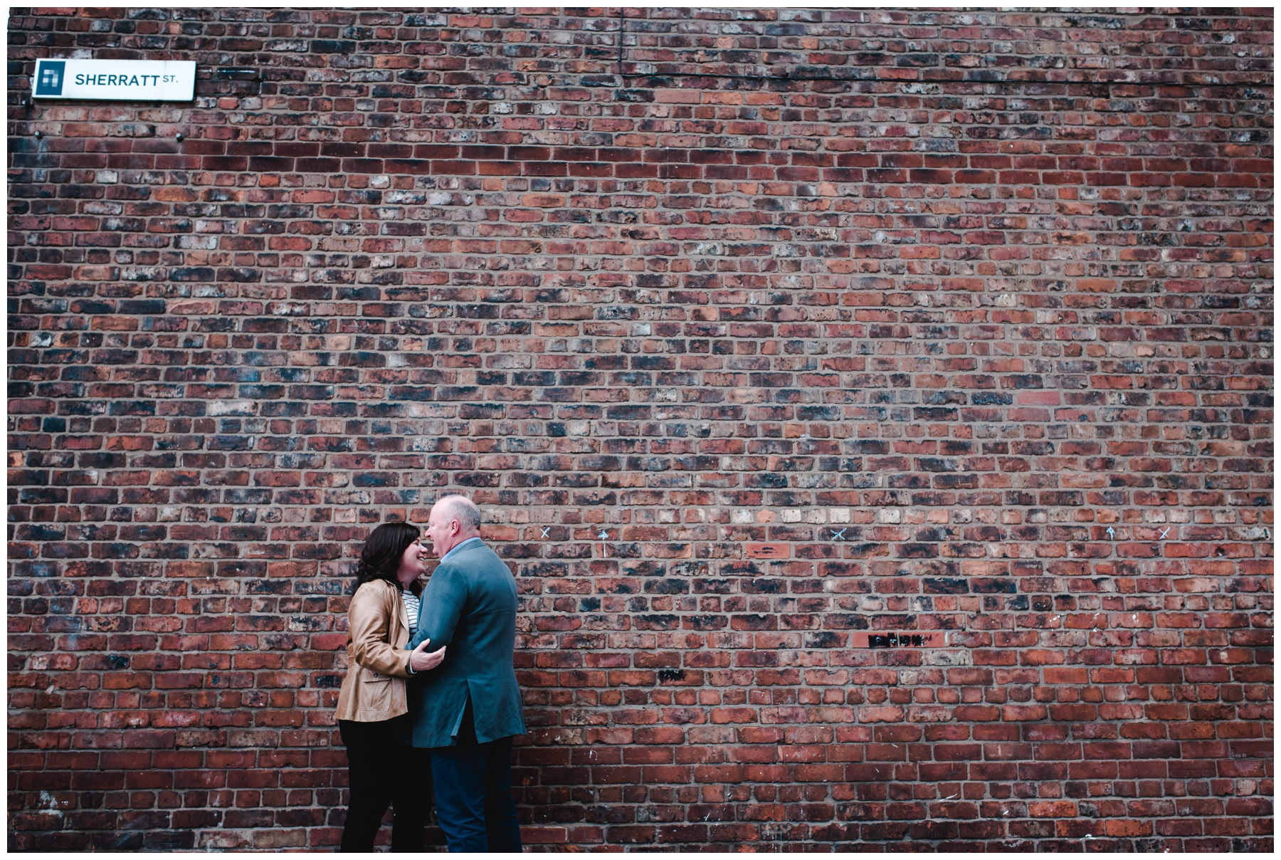 Carl and Allison in front of brick wall laughing in Northern Quarter in Manchester