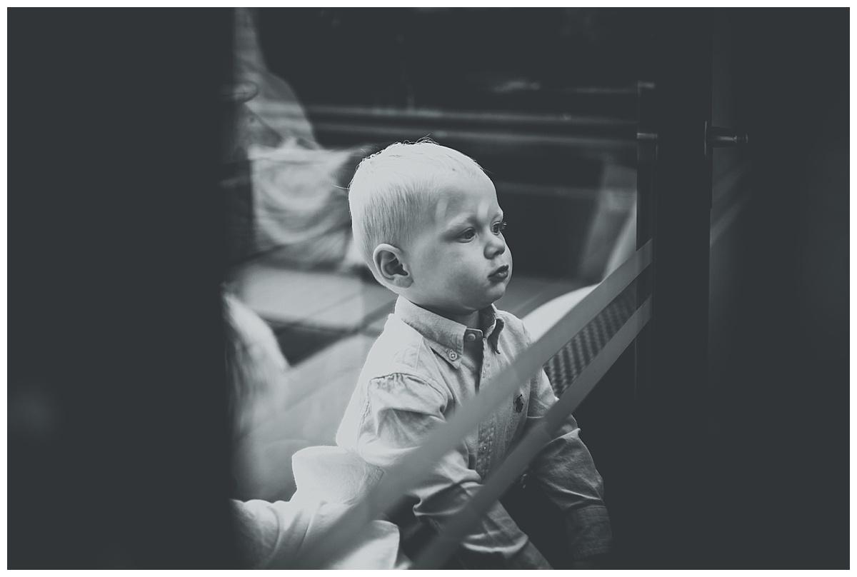 Little boy looking through window at Great John Street Hotel