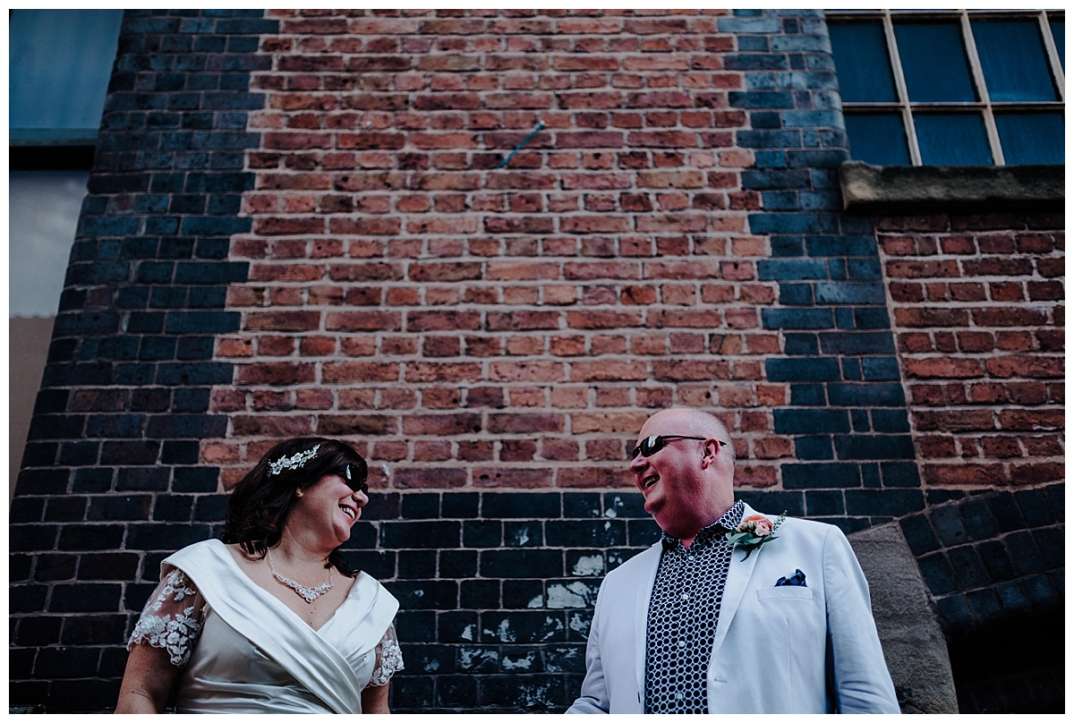 Carl & Allison in shades looking at each other in Manchester on wedding day
