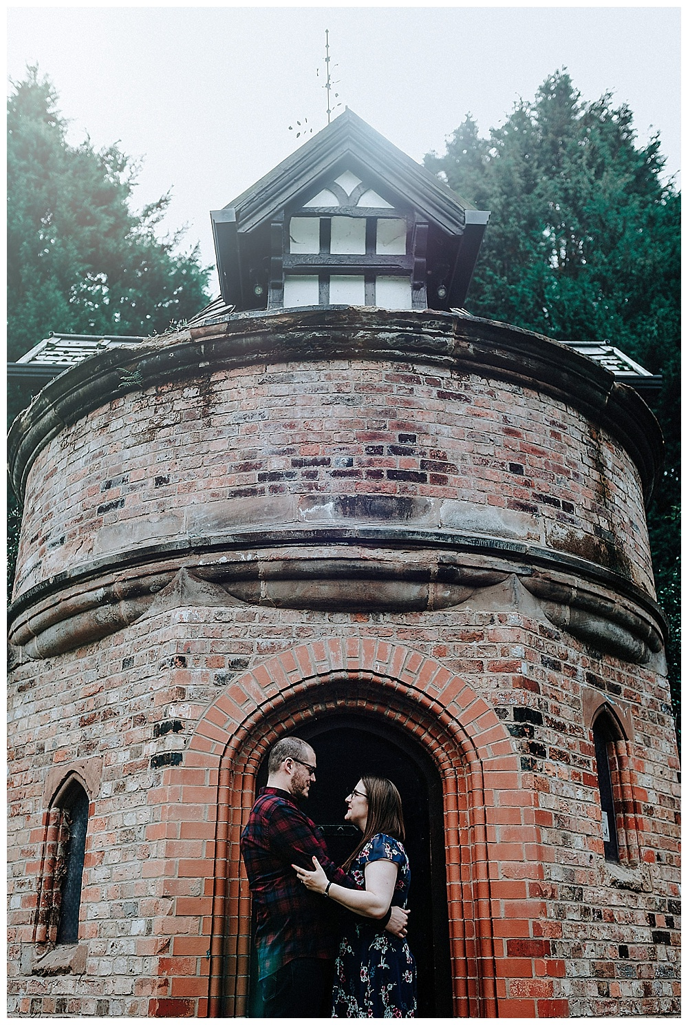 Louise and David looking at each other in front of the tower at Walkden Garden's in Sale