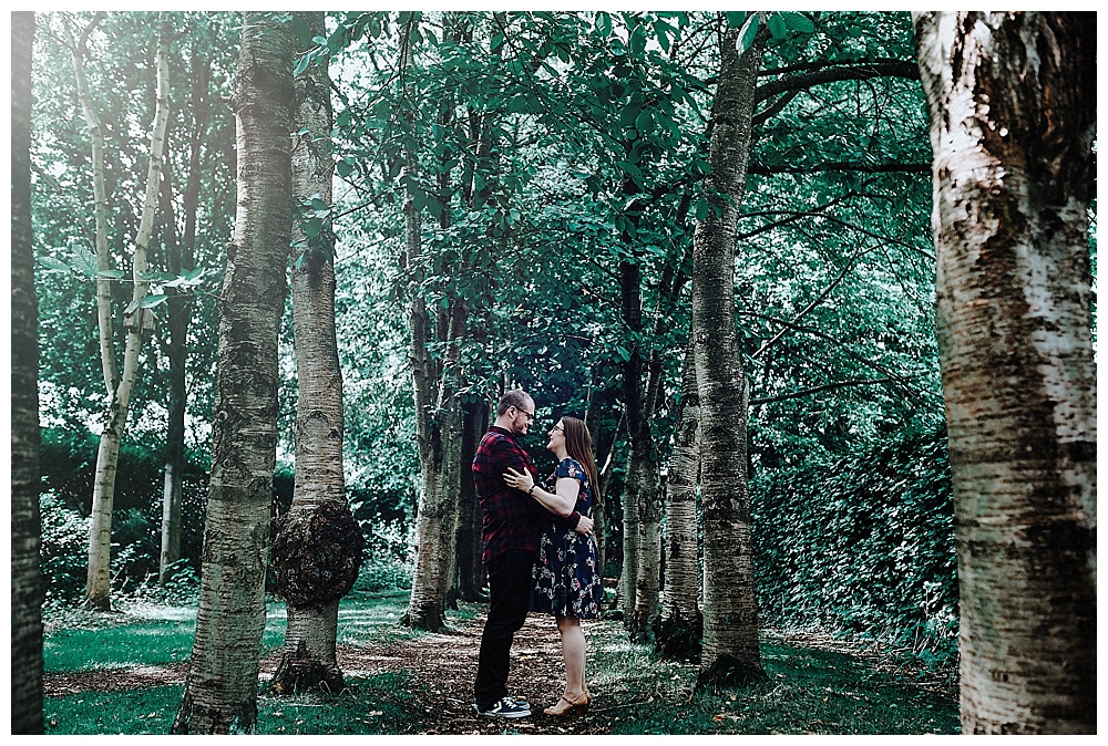 Louise and David in each others arms in the trees at Walkden Gardens in Sale