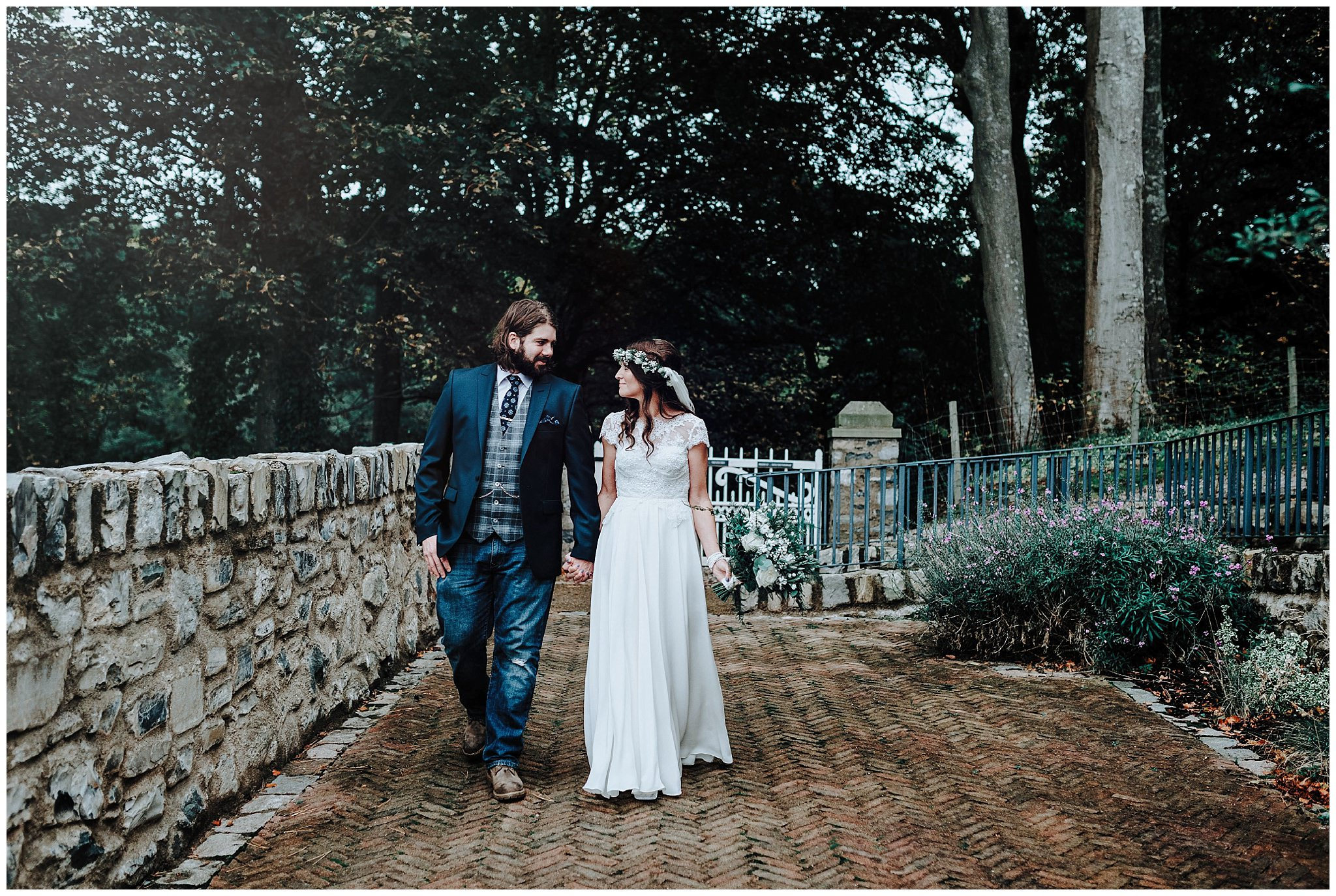 Bride and Groom walking hand in hand at Bodnant Welsh Food Centre