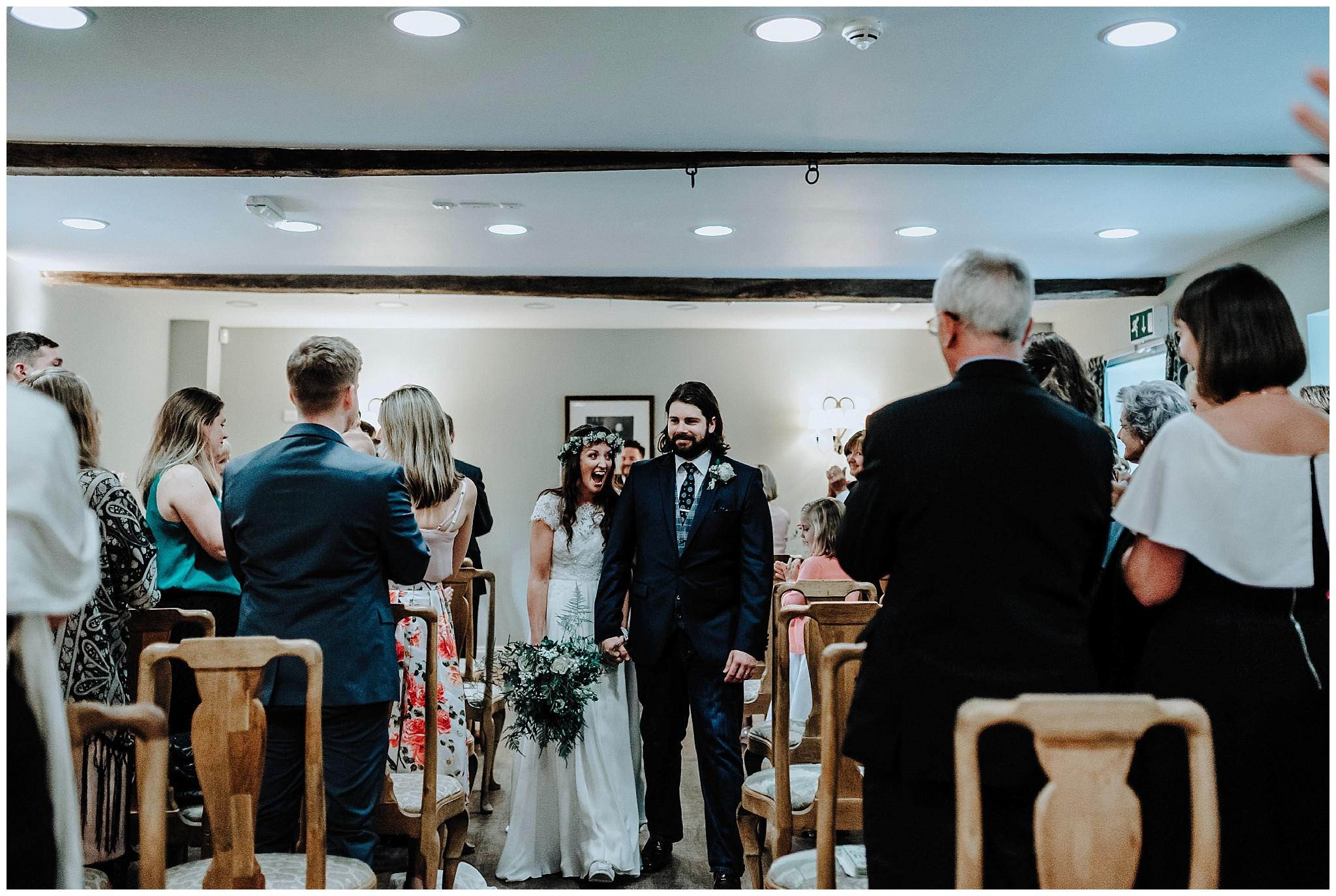 Bride and Groom walking back down the aisle together at Bodnant Welsh Food Centre