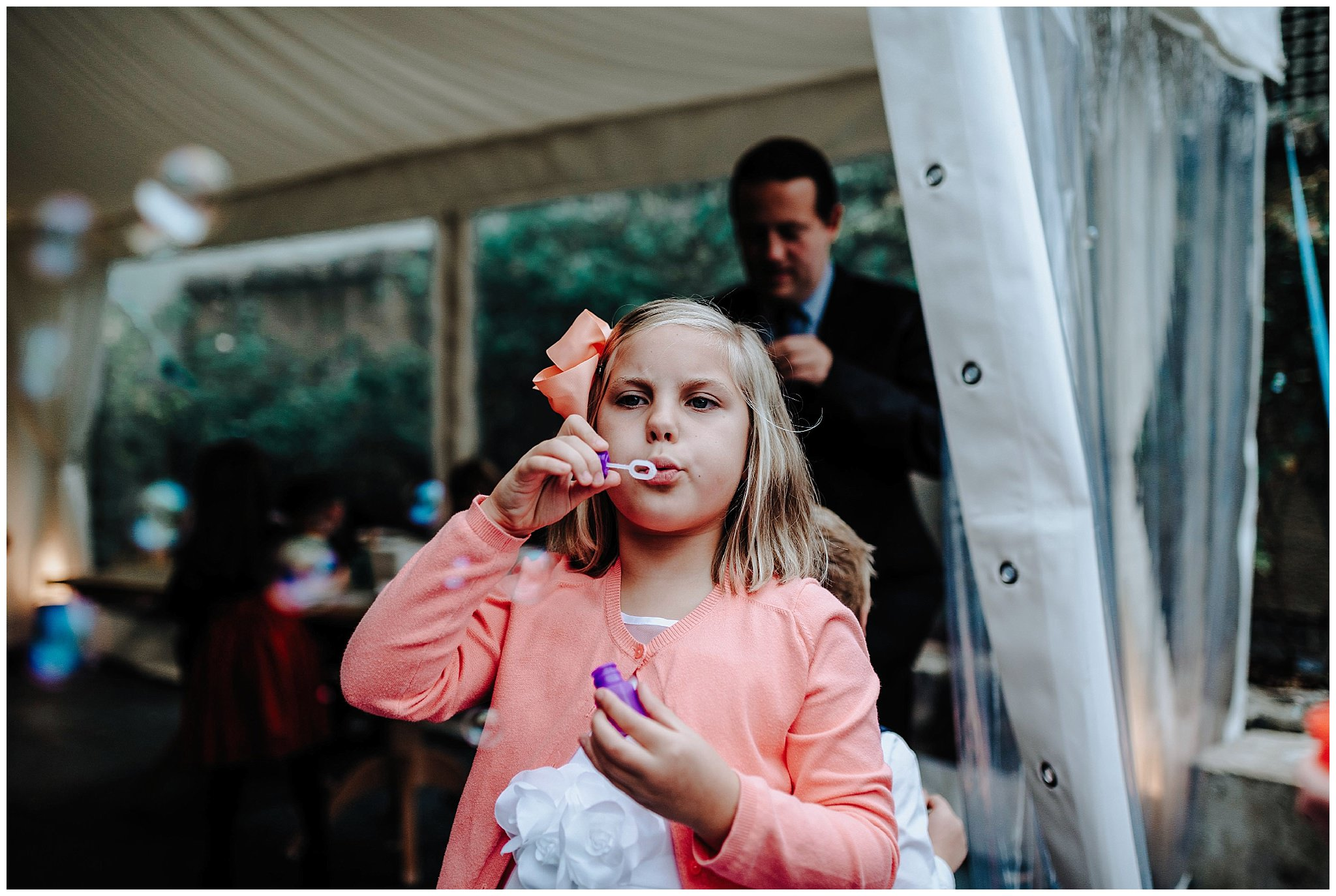 Little girl blowing bubbles at wedding at Bodnant Welsh Food Centre