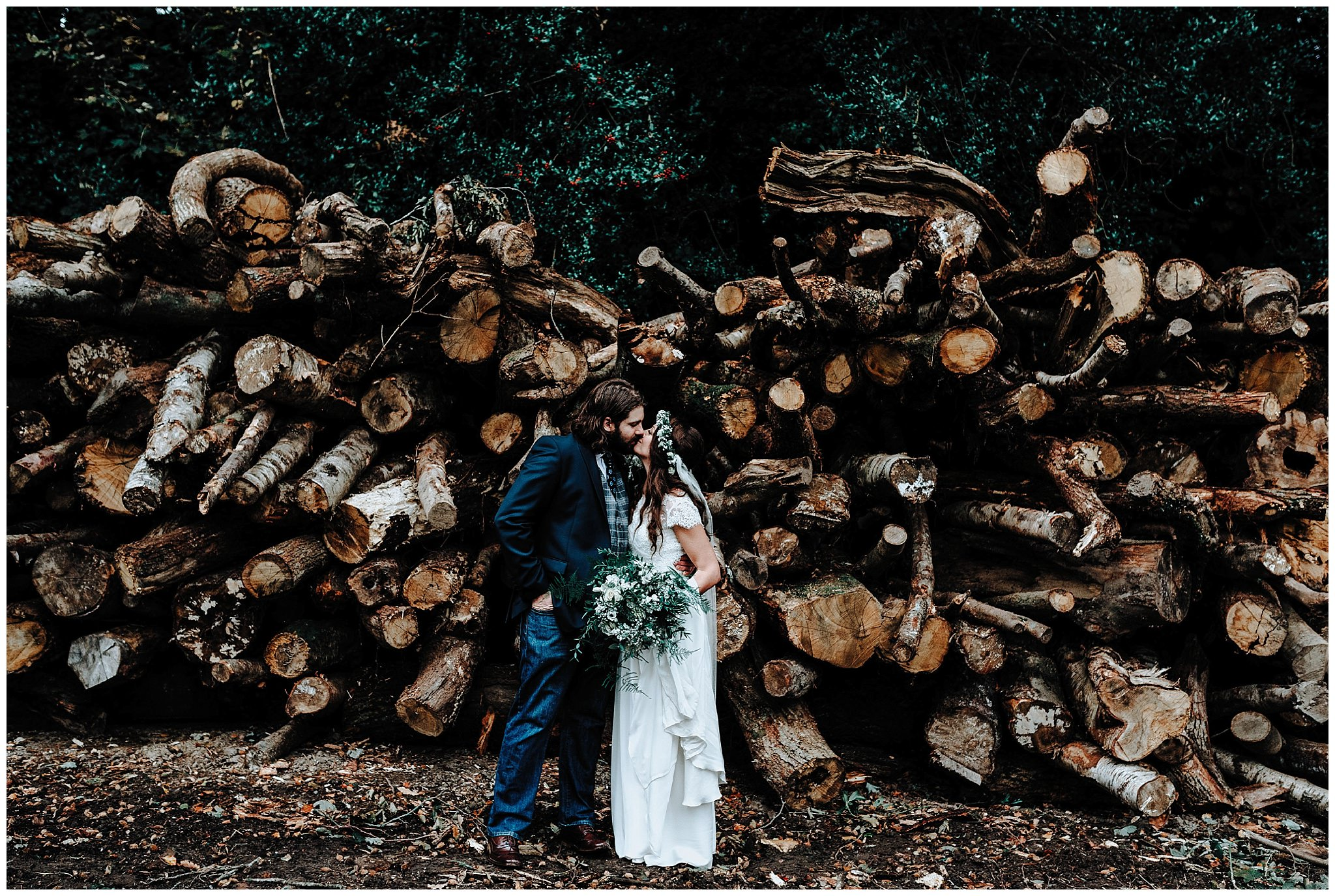 Bride and Groom kissing in front of logs