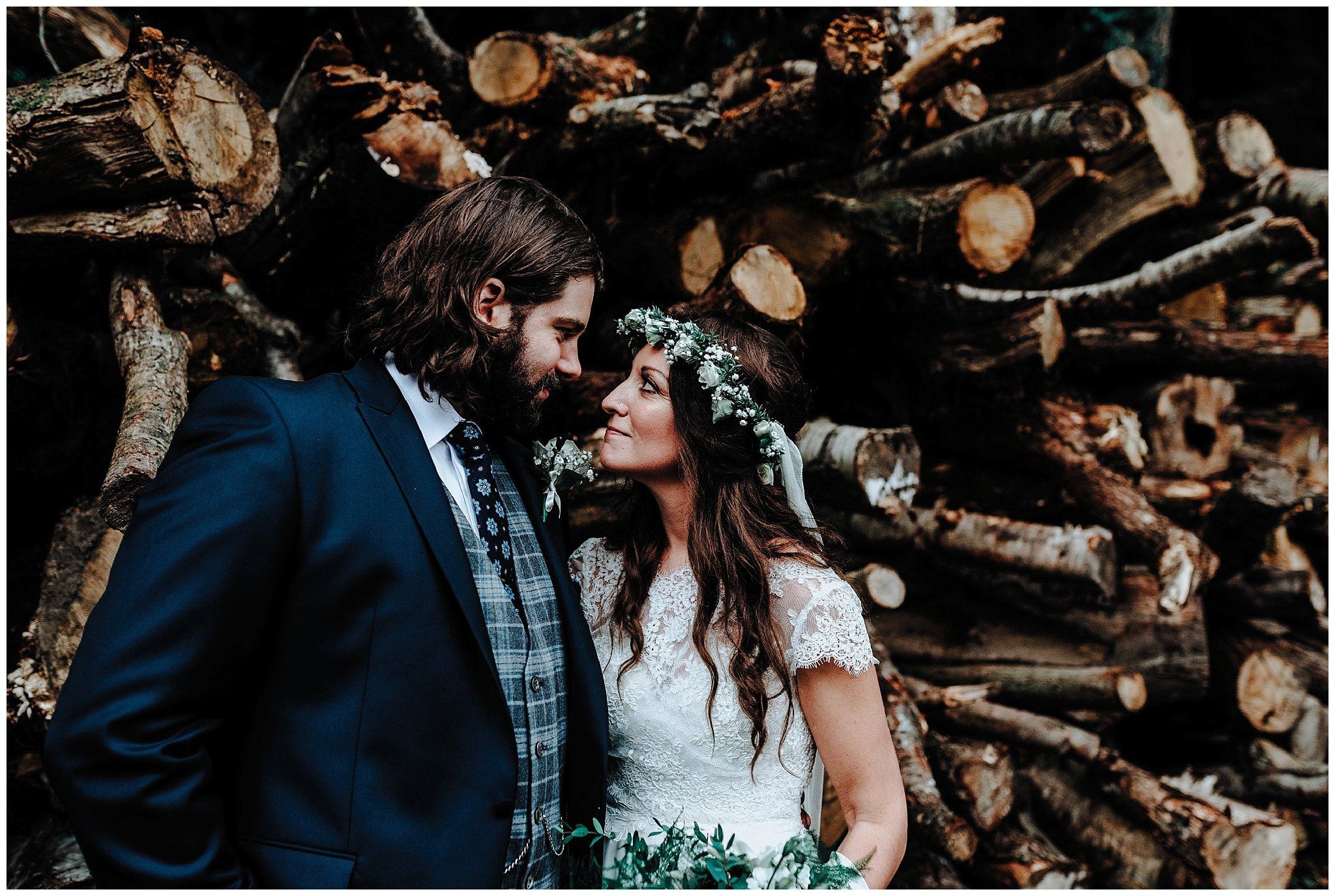 Bride and Groom looking at each other in front of logs