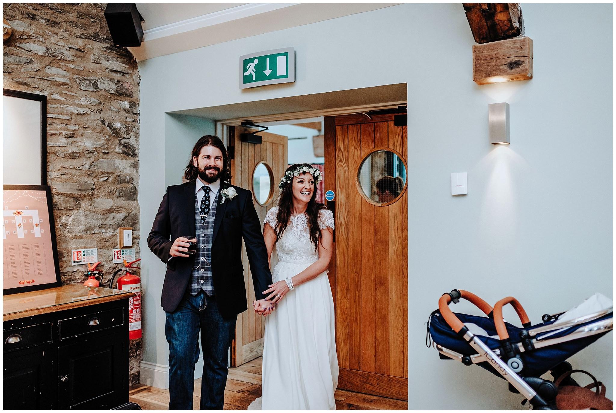 Bride and Groom walking in to wedding breakfast at Bodnant Welsh Food Centre