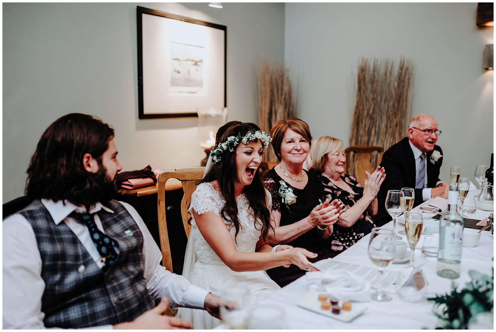 Bride laughing at joke during speeches at Bodnant Welsh Food Centre