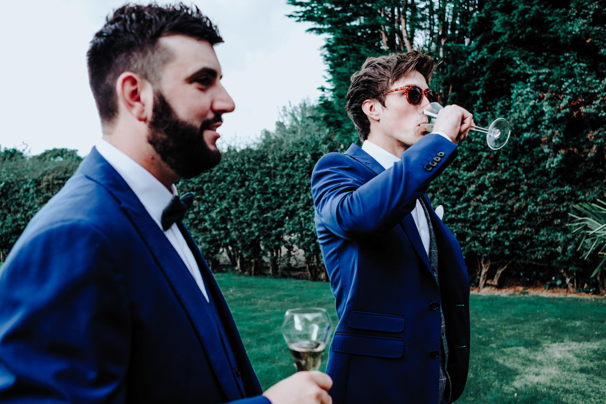 Groom drinking champagne during groom prep in Cheshire