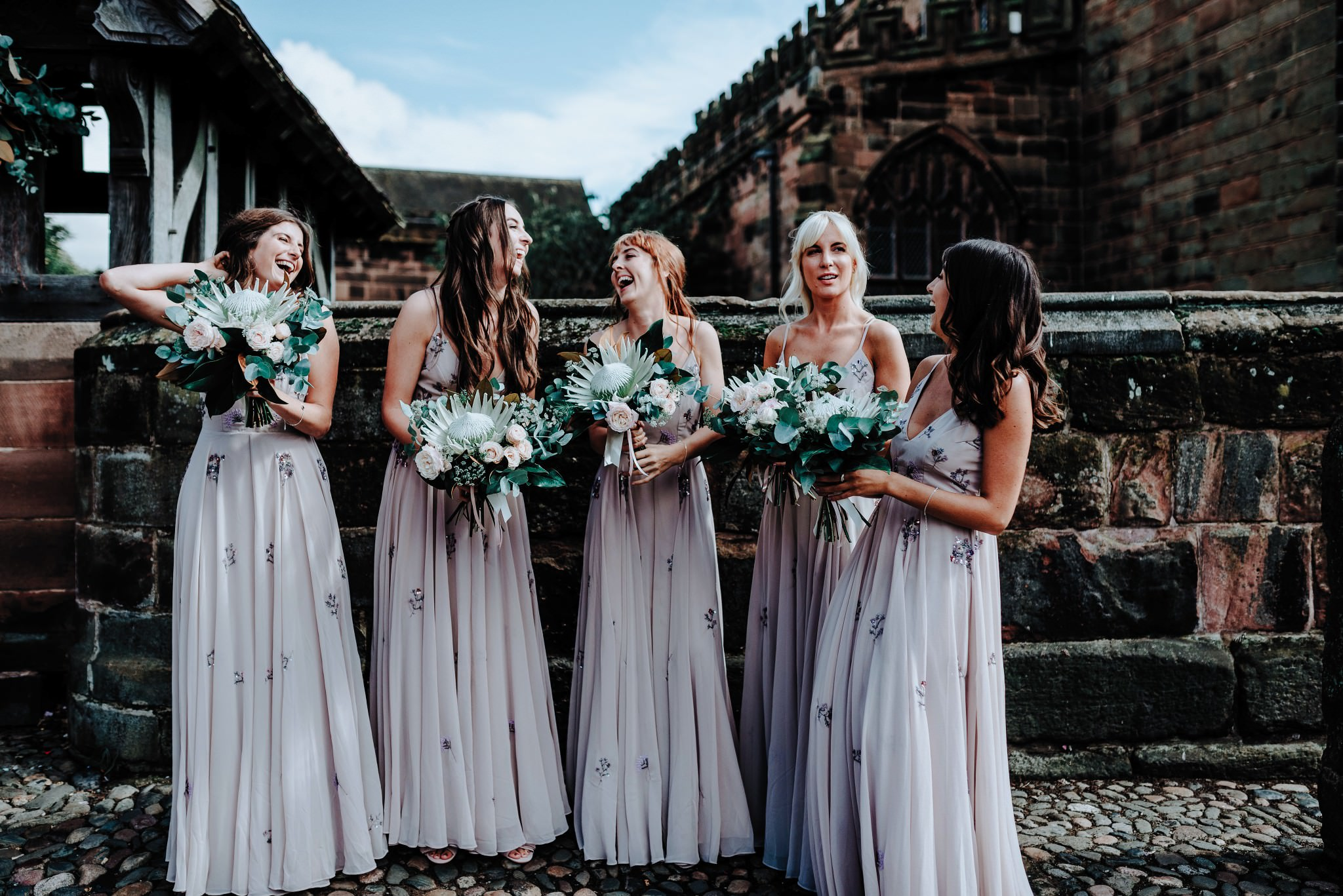 Bridesmaids waiting outside the church in Great Budworth in Cheshire