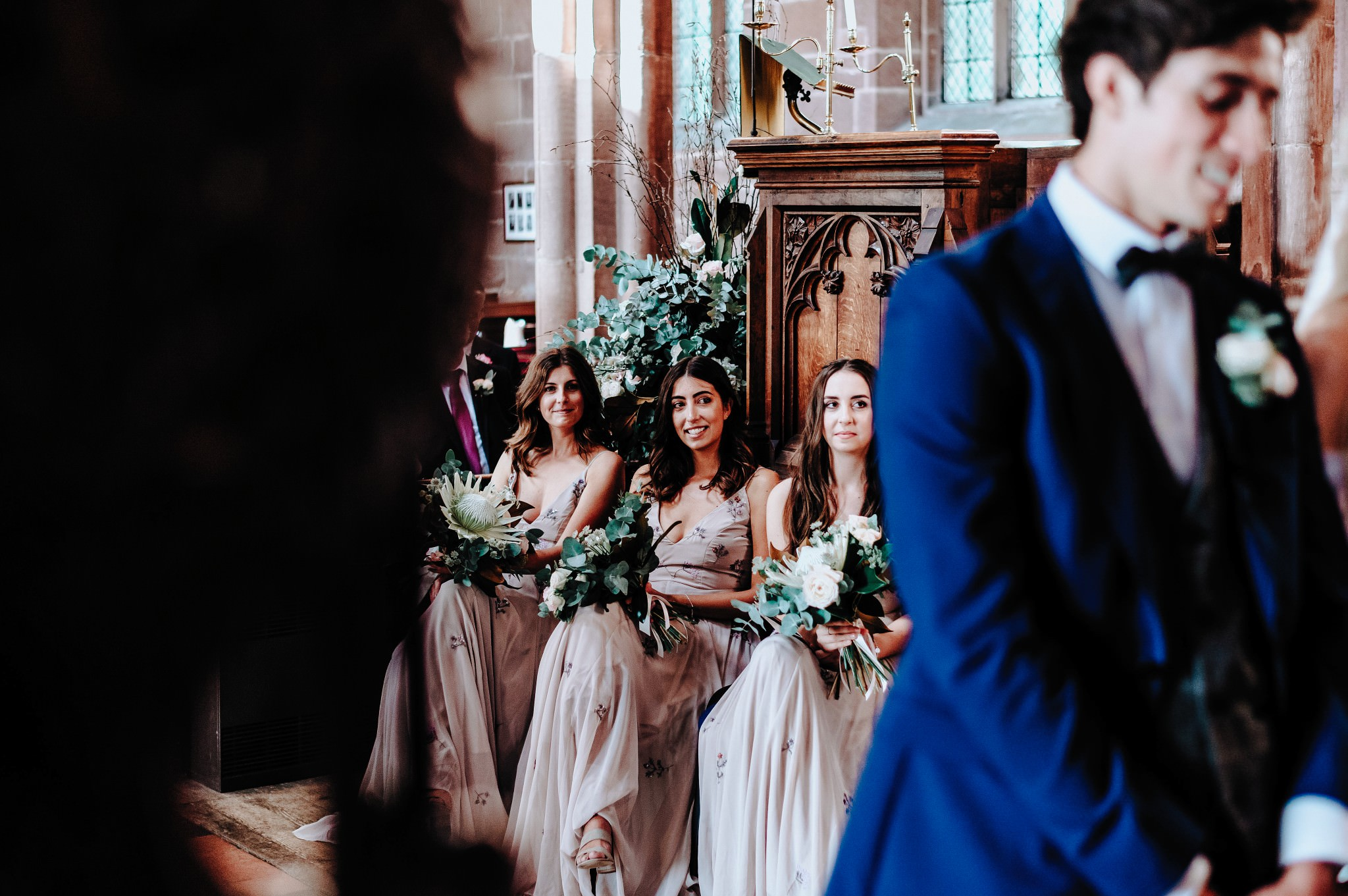 Bridesmaids looking onduring ceremony at Great Budworth church in Cheshire