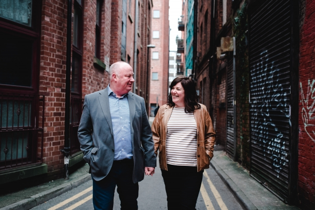 Allison & Carl walking hand in hand on their Manchester Engagement Session