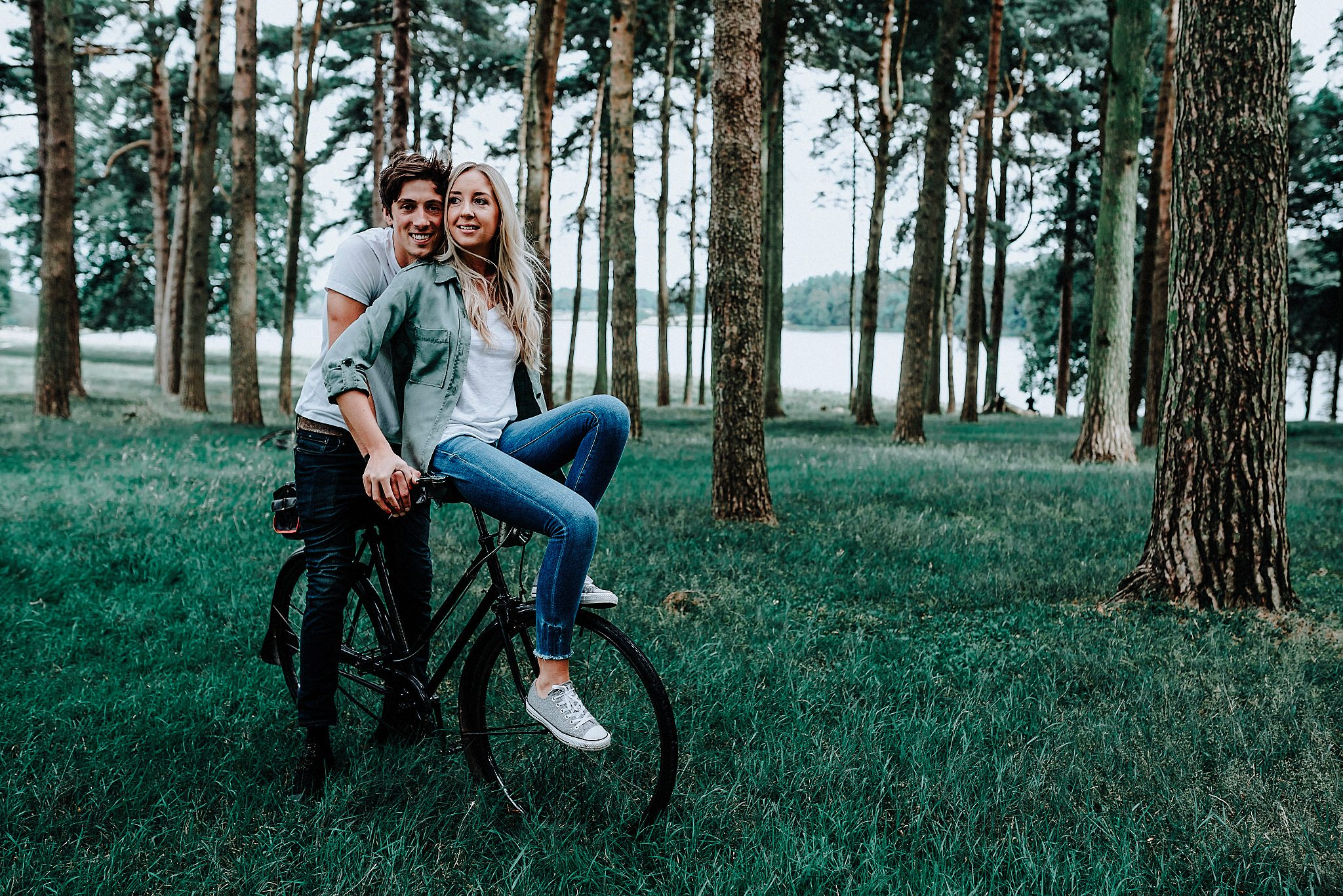 Lauren & Christopher smiling on a vintage bike in Tatton Park, Cheshire
