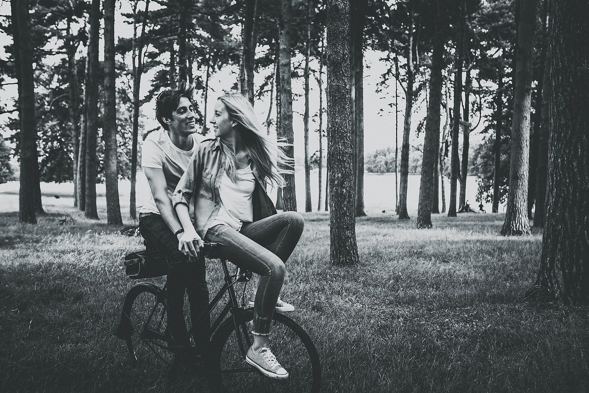 Lauren & Christopher looking at each other smiling on vintage bike at Tatton Park, Cheshire